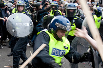 Police officer fighting rioters during the London riots 2011